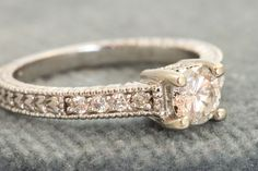 Offered for your consideration is a wonderful engagement ring. It is 14 KW gold with a 0.58 CT center Diamond and eight side Diamonds for @0.74 CT TW of Diamonds. The center Diamond is 'G-H' and VS2 and the side diamonds are well matched. It is size 6.5 but could be sized by your local jeweler. It weighs 3.8 grams and is in excellent estate condition.