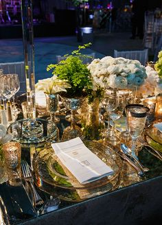 This place setting is made even more opulent with the use of votive candles and a mirrored tabletop.