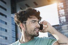 """Laden Sie das lizenzfreie Foto """"Germany, Cologne, Young man using cell phone, smiling"""" von firstflight zum günstigen Preis auf Fotolia.com herunter. Stöbern Sie in unserer Bilddatenbank und finden Sie schnell das perfekte Stockfoto für Ihr Marketing-Projekt!"""