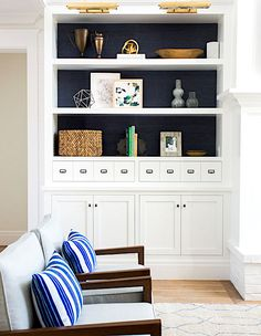 A surefire way to make your prized objets take center stage in a white built-in is to line the back of the shelves with black textured material or paint them matte black. | Designer: Studio McGee