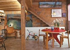 """Placas de OSB e pilares de peroba descartados na reforma do telhado compõem o mezanino. """"É onde as crianças dormem. Acomodo meus filhos e também os de minha namorada em colchões extras"""", diz o arquiteto Paulo Alves. Solução simples e de efeito, a parede de tijolos descascados revela sua beleza original."""