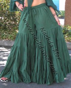 Dark green tribal fusion style belly dance tissue cotton tiered ruffle pants with an elastic drawstring waistband. 15 yard hem at leg bottoms and double layered in the top panel. Available in 3 sizes: Sm/Med, Lg/XL or XXL.
