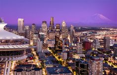 """Seattle from a helicopter, space needle, seattle skyline and mount rainier. The newest addition to our collection, """"Suspended"""" features the Seattle skyline, Mount Rainier and The Space Needle at sunset from a helicopter.  It features The Great Wheel and a couple of Washington State Ferries.  Shot by Clane Gessel"""