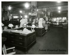 Children's Clothing Department inside The J.L. Hudson Company Department Store. Visible throughout the department are mannequins displayed atop retail tables, which feature the latest dresses for little girls. Accompanying the dresses are ladies hats and baby shoes. Visible in the background are cribs, carriages and outerwear.