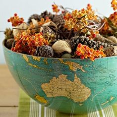 Cut an old globe in half and fill it with fall foliage