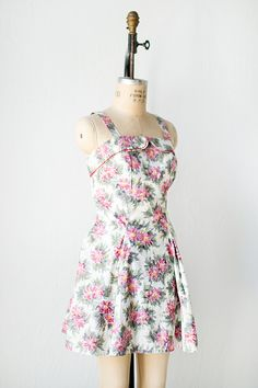 1950s romper mini dress made from a pink and white floral printed cotton. This summer mini dress features a sleeveless bodice with thin straps, a straight across neckline with flap detail. It is fitted in the bodice and waist and flares out at the skirt. Underneath the dress is a biult in strapless white romper with shorts made from a thicker white cotton. Via Adored Vintage.
