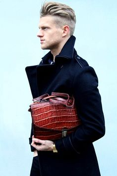 Brown Crocodile Bag, Black Wool Military Style Coat with Leather Piping, and Blonde Modern Military Hair. Men's Fall Winter Fashion.