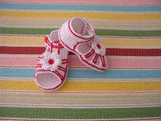 Sandalia en algodón blanco de crochet, ribeteada de rojo y adorno de flor blanca y roja.