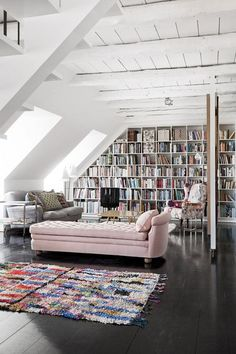 Feminine details, such as the pale pink chaise, nicely contrasted by the rustic, white-washed, beamed ceiling and dark wooden floor.