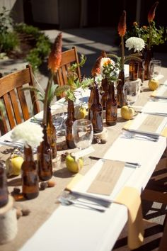 beer bottle centerpieces :) redneck meets classy w. the flowers! Prob wouldn't do it but not bad