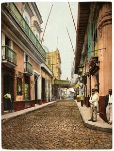 A view every tourist knows: Calle Obispo in La Habana Vieja. The shopping street today for tourists and place to sip a Mojito, before heading back to Varadero with your guáguá, the hand-colored photo is from 1900.Cuban Photograph Collection by the University of Miami Libraries.Image Public Domain.