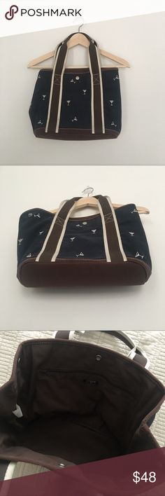 J Crew Martini glass tote Navy blue tote with little martini glasses with brown leather trim. Very good pre loved condition!! A little misshapen from being stored, but it will take it's shape again once it's in use. Perfect for a preppy summer with drinks! J. Crew Bags