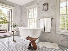 Bathroom with floor to ceiling tile, a freestanding tub, and a lambskin throw