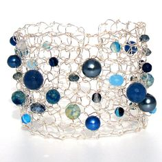 Lapisbeach Statement Jewelry. Unique modern metal cuff bracelet made from hand knitted metal. One of a kind as no two knit up the same. The Blue Agate semi precious faceted stones in different sizes mixed with crystals and pearls dance about with a mixtures of grays and silvers.