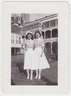 Two sweet 1st year nursing students pose in matching uniforms during the 1940s.