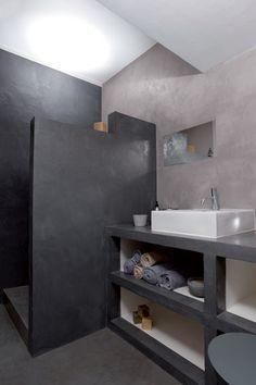 salle de bains réalisée en beton ciré pour les murs, la douche italienne ainsi que le plan de travail supportant une grande vasque blanche rectangulaire