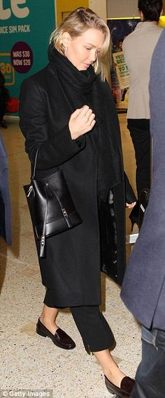 Rugged up: Lara was dressed in layers of black clothing when she arrived at Sydney airport...