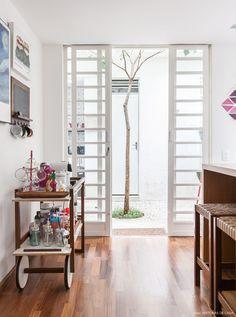 Cozinha tem balcão central e carrinho de chá de madeira que abriga uma das coleções da moradora.