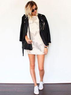 Look com vestido off white + jaqueta biker de couro + tênis branco.