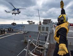 PHILIPPINE SEA (Nov. 19, 2017) Boatswain's Mate 3rd Class Vincent Tate signals an SA 330 Puma helicopter assigned to the dry cargo and ammunition ship USNS Wally Schirra (T-AKE-8), during a vertical replenishment (VERTREP) with the forward-deployed Arleigh Burke-class guided-missile destroyer USS Stethem (DDG 63) during Annual Exercise 2017 (AE17). AE17, the premiere training event between the U.S. Navy and the Japan Maritime Self-Defense Force