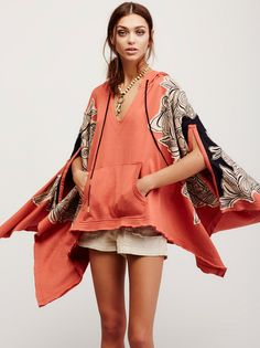 Bungalow Poncho   In an oversized silhouette, this hooded poncho features beautiful floral applique detailing with embroidery and slits on the sleeves.  V-neckline and front kangaroo pocket with allover raw trim and a high low hem.