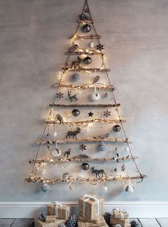 graduated tree branches are hung by jute, wrapped with string lights and decorated with ornaments