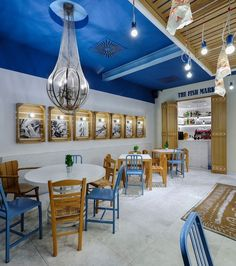 """At Fish Market, a seafood restaurant in Limassol, Cyprus by fishing references range from the net repurposed to encase a chandelier to the lightbulbs used as """"bait"""" on iron hooks bobbing overhead. Beach Restaurant Design, Deco Restaurant, Restaurant Interior Design, Seafood Restaurant, Cafe Interior, Seafood Boil, Interior Ideas, Interior Decorating, Interior Design Magazine"""