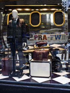 Prada menswear  A great vintage style display, from the merchandise to the backdrop, and from the props to the floor panel. Loving how the visual merchandiser fit a part of a WWII aircraft into such a space limited window.