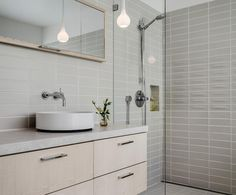 A band of Crease Out Dimensional tile adds texture to this sleek bathroom in M1 Canvas (variation 1).Ceramics