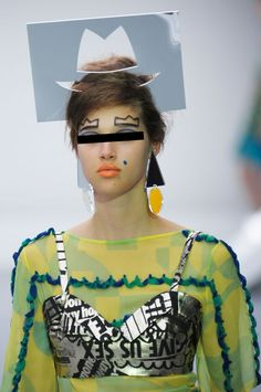 Beauty DON'T: Stenciled-In Eyebrows  For a moment, let's just ignore this model's blue beauty mark, crazy outfit, and stencil-as-hat to focus on her drawn-on crown-shaped brows. Is this pic from a fashion show or a babysitting experience gone wrong?