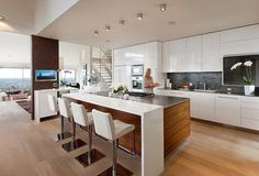 The glossy contemporary kitchen works best for an owner(s) who entertains often. A walnut island base and hardwood floors warm up the space, which also has a sleek white lacquer bartop and a stainless island countertop. Contemporary, warm and open.