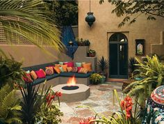 The exotic style of the outdoor space below begins with the stone and river rock flooring laid in a pattern that looks like a Moroccan rug. Cement is also used for the base of the seating area and the fire pit, which ties it all together.