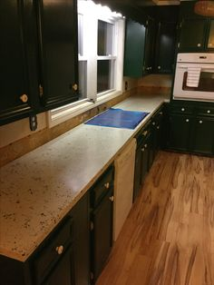 Polished white concrete counter-tops with green glass.