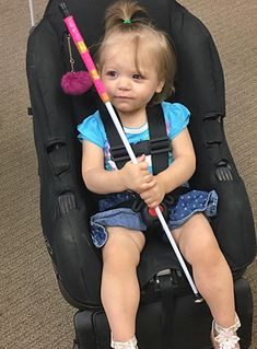 A small child sits in a car seat, holding her cane.