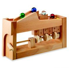 """A mechanical wooden marble track for the transport of balls or marbles. Turn the crank to propel the large glass marbles up to the top of the wooden """"escalator,"""" where they roll down and advance in queue for another ride. Makes a great clacking sound as marbles bump and knock the wood! A clever heirloom […]"""