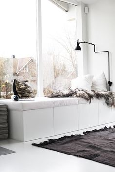Aranżacja wnętrza w kolorze białym z siedziskiem przy oknie