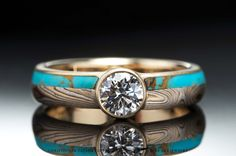 This stunning ring features 14K yellow gold, sterling silver, and shakudo (2k red) mokumé gane, with turquoise inlay and a diamond.