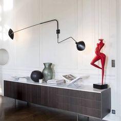 L'intemporelle applique murale 2 bras pivotants dont 1 courbe Mouille de coloris noir a été dessinée en 1954 par un des plus grands designers de luminaires du 20ème, Serge Mouille: une véritable icône du design qui habille le salon, la chambre ou une autre pièce de la maison, avec ses deux bras: l'un d'1m75 et l'autre d'1m13...Un classique du design qui ne passe pas inaperçu.<br><br>Son corps est en acier, les rotules en laiton sont pivotantes à 270° et les réflecteurs en aluminium sont…