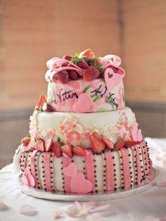 Pastel de boda pequeño, decorado con fresas, detalles rosas asimétricos, corazones y la firma de los novios