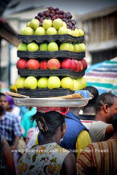 Vendor balancing trays of fruit on head - Kumasi, Ghana
