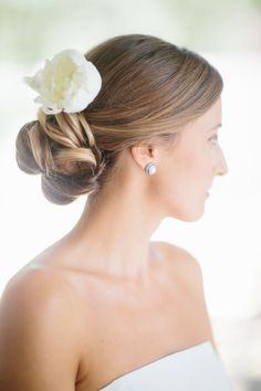Hairstyle: Low wrapped bun with a flower. See the wedding on SMP: http://www.StyleMePretty.com/california-weddings/2014/02/27/classic-black-tie-durham-ranch-wedding/ Photography: Annie McElwain