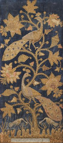 A metal thread embroidered velvet panel from Northern India, circa 1900. The blue velvet ground profusely embroidered with silver and gold thread with a flowering plant & two perching peacocks; beneath the plant, a pool and two stalks.