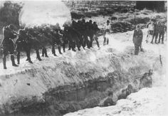 Einsatzgruppen soldiers shooting Jews who are in a ditch.