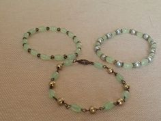 Bracelet group. Jade colored glass ovals. Antique Gold spacers. Light green pearls and gold metal beads. 2 are strung on stretch cord. One is individual links