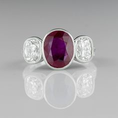 A gorgeous deep red, oval Burmese Ruby weighing 3.13 carats is situated between two stunning, superior quality antique cushion diamonds in this newly created Edwardian style handmade platinum setting. An extraordinary and impressive treasure.