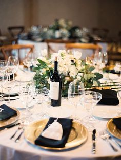 white table cloth, gold charger, black napkin, b+w striped runner