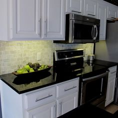 Carrera Marble Backsplash, black counters, white cabinets