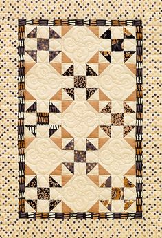 Coffee-color prints provide a neutral palette for gorgeous quilting. Combining Shoo Fly and Snowball blocks adds visual interest and makes the wall hanging look more scrappy.