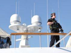Man with gun on yacht - credit Horst Ruetten.png (470×352)