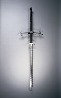 1550-1600 German two-handed sword with flamboyant blade - steel, leather and wood grip with brass rivets, bronze pommel (overall 66 7/16 in., 2.98 wt., blade 46 11/16 in., quillions 19 7/8 in., grip 19 5/16 in., ricasso 10 1/2 in.) - Cleveland Museum of Art 1919.71